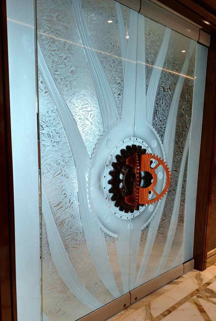 Frameless Doors with Carved and Gluechipped Glass gears by Sans Soucie